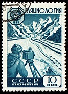 Researcher with device in mountain on post stamp