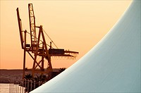 Cranes and detail of canvass tent, Concept image, the harbour seen at sunset Alicante Spain