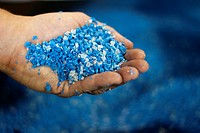 Recycled blue and white plastic ´nurdles´ shredded plastic raw materials ready to be loaded into the hopper of a plastic molding injection machine