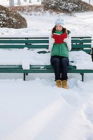 Woman in warm clothing reading book on a snowy bench