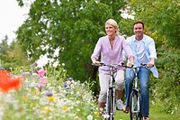 Couple riding bicycles in wildflower field