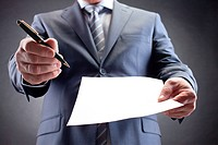 Close_up of businessman holding paper and pen and giving them for signature