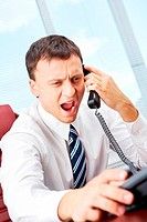 A manager sitting at table and shouting in telephone receiver