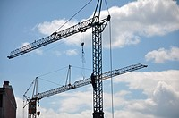 cranes on construction site with a background of blue sky
