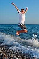 jumping teenager boy on stone seacoast