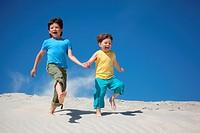 Two boys run on sand