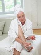 Senior woman painting toenails, close up
