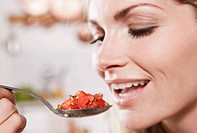 Italy, Tuscany, Magliano, Young woman eating spoon of chopped tomatoes, smiling
