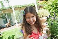 Germany, Bavaria, Girl blowing soap bubbles in garden, smiling, portrait