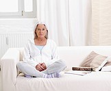 Germany, Hamburg, Senior woman sitting on sofa, portrait