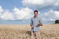 Germany, Bavaria, Altenthann, Man standing in wheat field, smiling, portrait