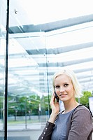 Germany, Bavaria, Munich, Young woman with cell phone, smiling