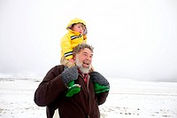 A portrait of a grandfather carrying his grandson on his shoulders through the snow, Kamberg, KwaZulu_Natal Province, South Africa