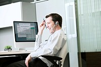 Business man with headset by computer in office