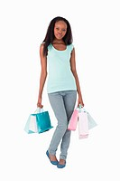 Young woman with her shopping on white background