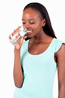 Young woman looking into her glass of water against a white background