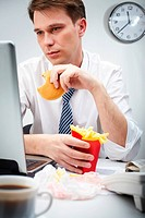 Portrait of serious businessman looking at laptop screen while eating hamburger and fries potato