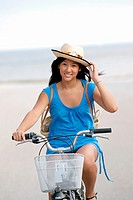 Cute young asian woman riding her bicycle