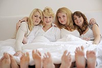 Four young women lying in bed