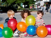 Cheerful friends with multi_coloured inflatable spheres outdoors