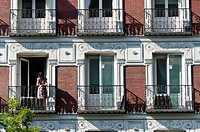 Woman look at from her balcony. Building Facade at Alcala street, Madrid, Spain