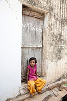 Young girl sitting on a doorstep - Shyampura Village, Rajasthan, India