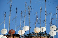 tv aerials and satellite dishes on rooftop