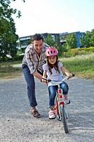 Father holding daughter on bike outdoors