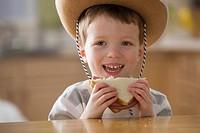Caucasian boy in cowboy hat eating sandwich