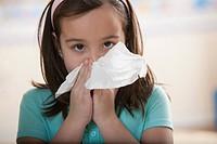 Caucasian girl blowing nose
