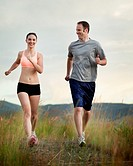 Caucasian couple running together on remote path