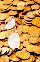 Many coins and reading glasses as business concept