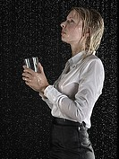 Businesswoman collecting rain in glass
