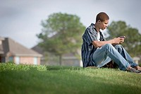 Mixed race teenager sitting in grass text messaging on cell phone