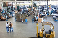 Workers reviewing paperwork in factory