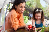 Mixed race mother and daughter tending garden