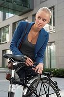 Germany, Bavaria, Teenage girl fixing lock of bicycle