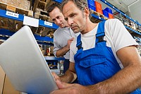 Germany, Bavaria, Munich, Manual workers using laptop in warehouse