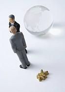 Glass globe, miniature businessmen, and yen sign