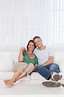 Germany, Munich, Couple sitting on couch, smiling, portrait