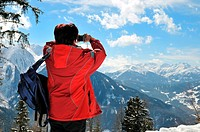 Senior woman taking picture with camera in mountain winter snow landscape