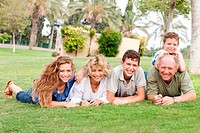 Portrait of a happy family lying down on the green grass in park
