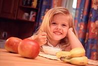 Small fair Pre_Teen girl is at the table mitt fresh fruit and eats a yogurt