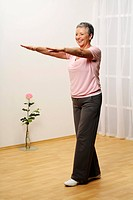 older woman standing in a room reaching out her arms _ tandem_stand _ the toe is touching the heel _ balance _ senior