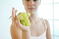 Young woman holds a bunch of grapes..