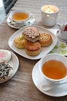 a close_up view of a cup of tea and mooncakes