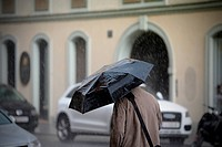 This photograph represents a man walking with umbrella, rear view. Useful file for your newspaper weather concept, vulnerability concept. Soft DOF.