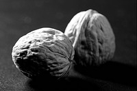 Walnuts with shells over black background