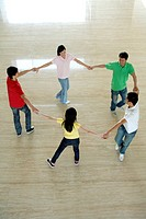 Top view of a group of young people making a circle hand in hand