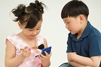 a little girl and boy with make_ups